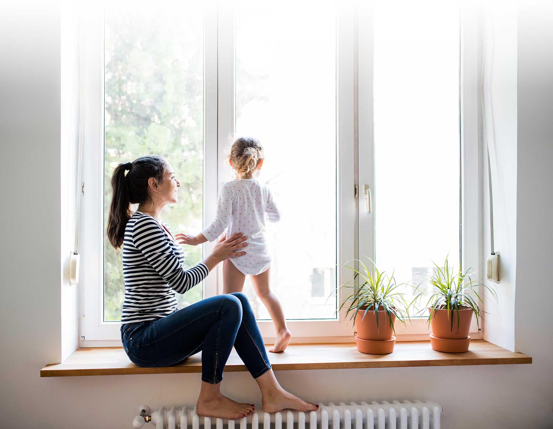 Mutter mit Kind sitzend auf Fensterbank und Heizung